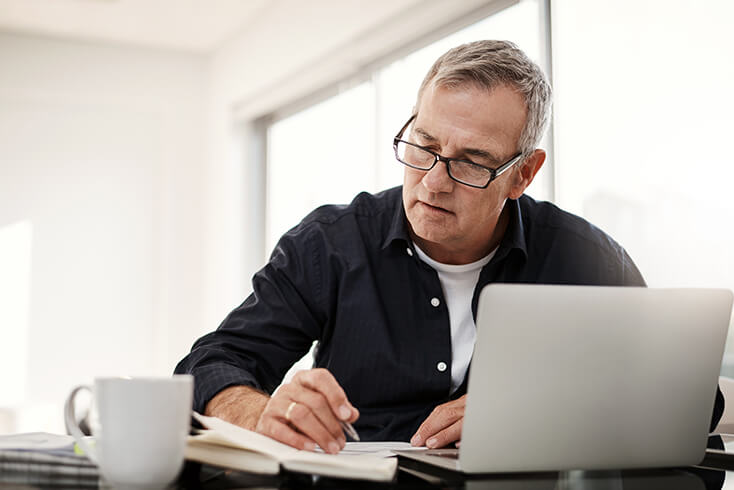 man looking through personal tax papers with coffee mug and laptop computer.